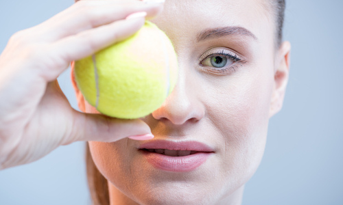 Woman with tennis ball covering eye