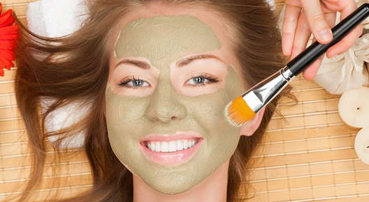 Image of a woman smiling with a facial mask.
