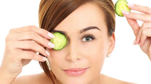 Image of a woman holding a cucumber slice to one of her eyes.