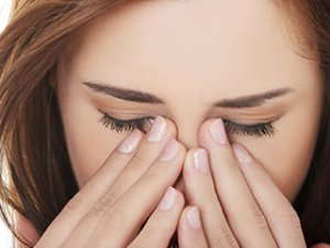Image of a woman rubbing her eyes.