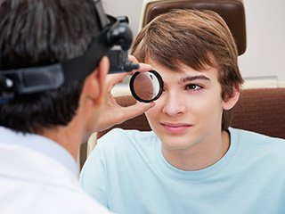 Image of an optometrist examining a teenage boy.
