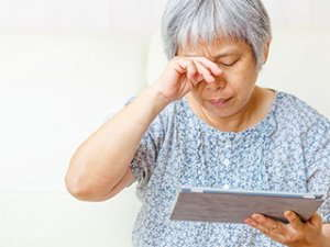Image of an elderly woman rubbing her eyes.