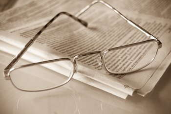 Image of glasses resting on a newspaper.