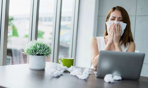 Woman at work suffering from allergy symptoms