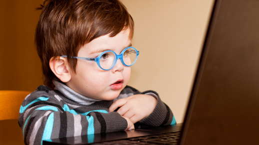 boy with glasses on laptop