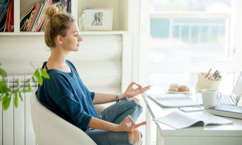 Woman meditating in home office space