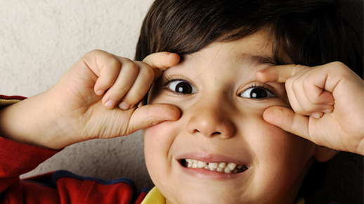 boy holding eyelids open with fingers