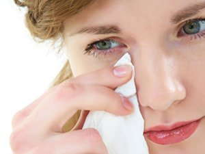 Image of a woman holding a tissue to her eye.