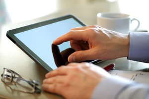 Image of hands using a touch screen tablet.