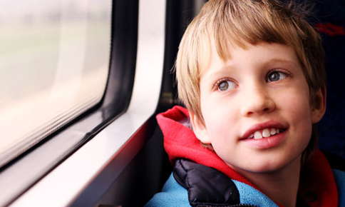 An image of a child with autism, who is riding on a train looking out the window.