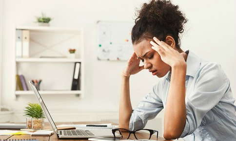 Woman experiencing a headache at work