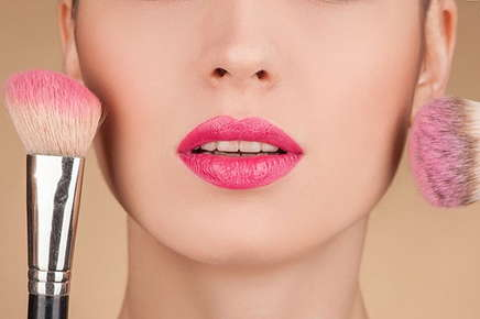 Image of a person wearing lipstick and holding a brush blush.