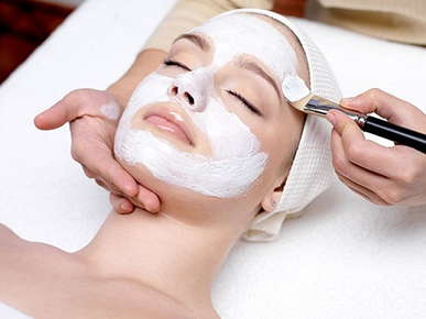 Image of a woman receiving a facial mask.
