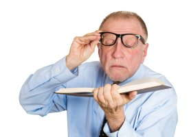 man reading with glasses pushed off face