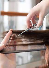 Image of hands trimming long hair.