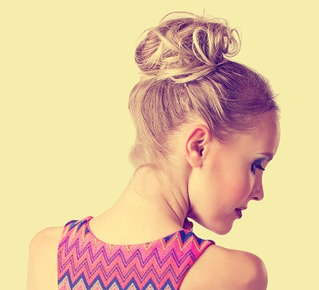 Image of the back of a woman's head with her hair tied up in a messy bun.