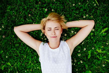 image of relaxed woman laying in the grass