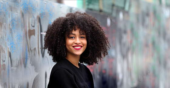 Image of woman with curly hair smiling.