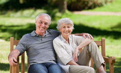 An image of a retired couple sitting on a park bench and smiling.