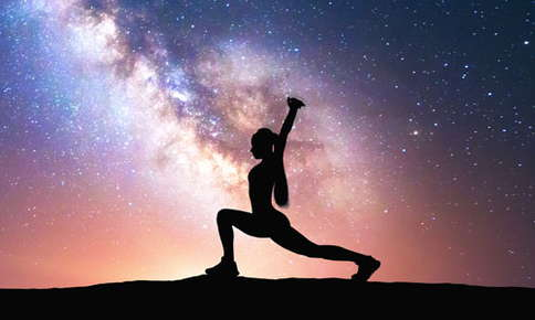 An image of a female silhouette doing yoga atop a mountain. Behind the figure is a galaxy swirl of stars and emission nebulae.
