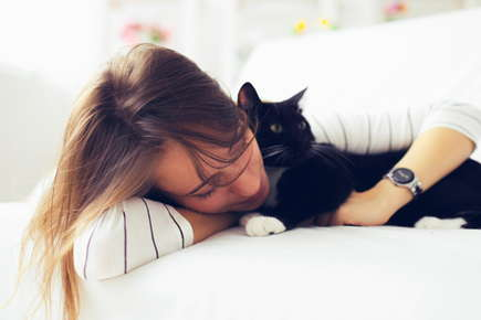 image of a lady cuddling a cat.