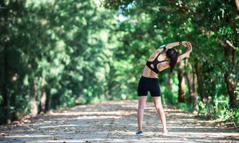 An image of a woman doing a stretch with her hands clasped and her arms stretched upwards. She's wearing workout attire while on a shaded trail surrounded by trees.