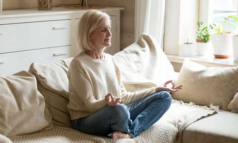 Older woman meditating on couch at home