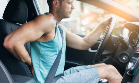 Man having back pain while driving car