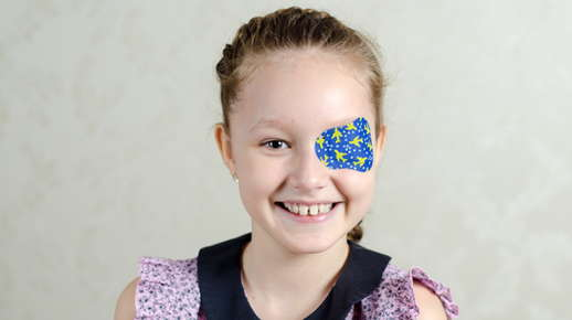 Image of a little girl wearing an eyepatch and smiling.