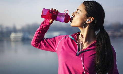Woman stopping to drink water while on a run