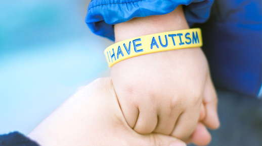 Image of a child's hand wearing an autism bracelet.