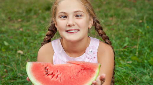 Image of a child with crossed eyes holding a watermelon.