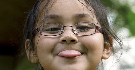 Image of girl wearing glasses and sticking tongue out.