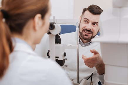 Image of a male patient asking his eye doctor questions during an exam.