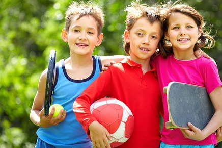 An image of a group of three elementary school-aged children, each holding a piece of sports equipment.
