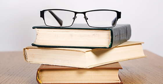 Image of glasses on a pile of books.