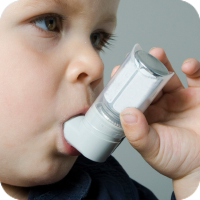 image of young boy using an inhaler