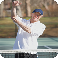 image of man at a tennis court holding his elbow