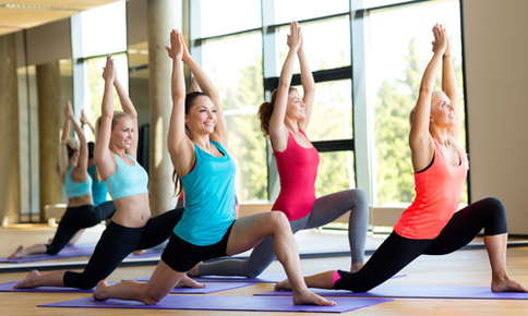 An image of a group yoga class. The group is in a pose where they're kneeling with their arms raised above.