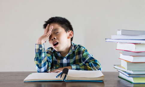 Image of a child who has a book open in front of him and appears to be frustrated and tired.