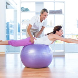 A chiropractor helps her patient exercise on an exercise ball