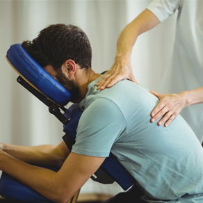 Chiropractic patient receiving a back treatment as his face rests in a face cradle