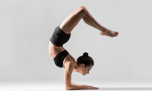 Woman doing scorpion handstand pose