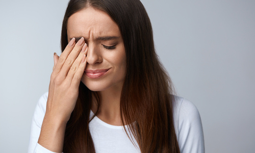 Woman experiencing eye pain