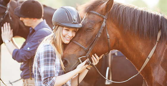Image of woman hugging horse.