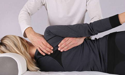 Woman receiving a back adjustment
