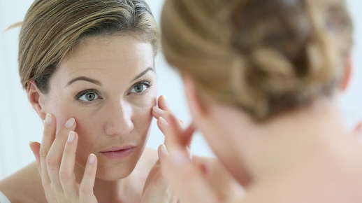Image of an older woman examining her face in a mirror.