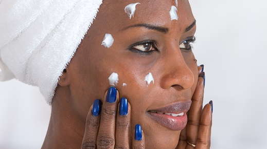 Image of a woman applying face moisturizer.