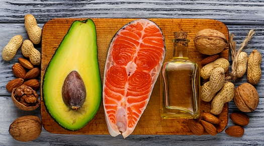 Image of an avocado, nuts, and oil laid out on a cutting board.