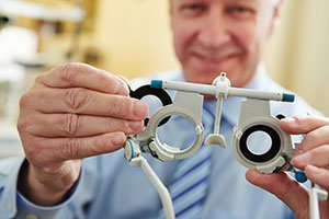 Image of an optometrist holding an eye examination tool.